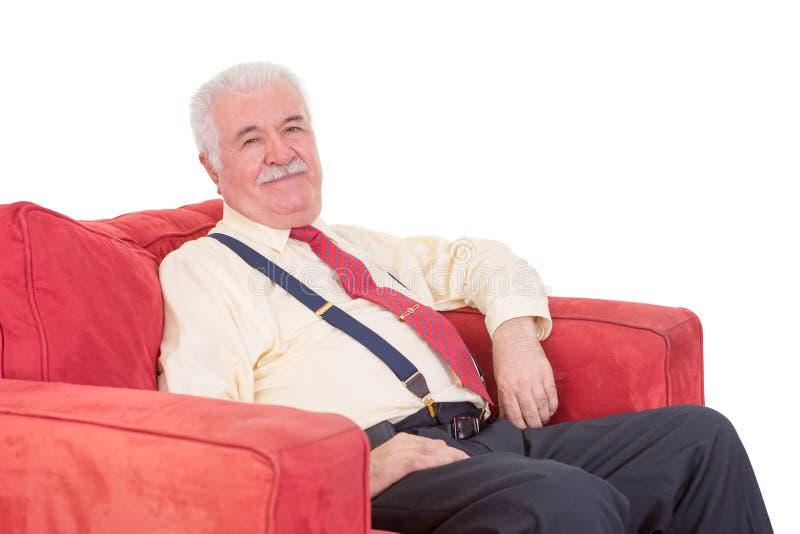 Älterer Herr, der in einem Lehnsessel sich entspannt stockfoto