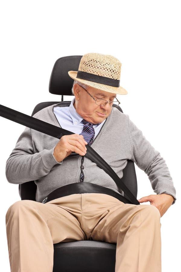 Älterer Herr, der einen Sicherheitsgurt befestigt stockfotos