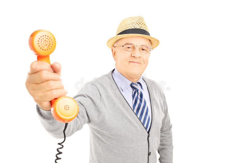 Älterer Herr, der jemand ein Telefon zum Gespräch gibt stockfotografie