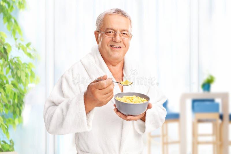 Älterer Herr, der zu Hause Getreide isst stockfotos