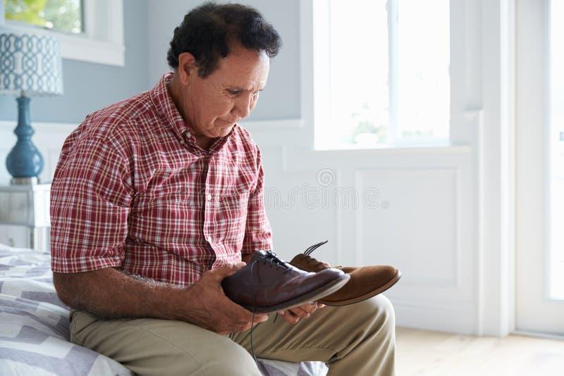 Älterer hispanischer Mann, der mit der Demenz versucht anzukleiden leidet stockfotografie