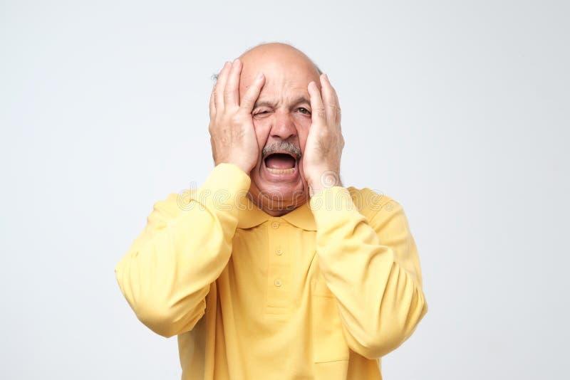 Älterer hispanischer Mann im gelben T-Shirt, das Haut auf Gesicht mit den Händen zieht Er ist vom Druck erschrocken oder ermüdet stockfotografie