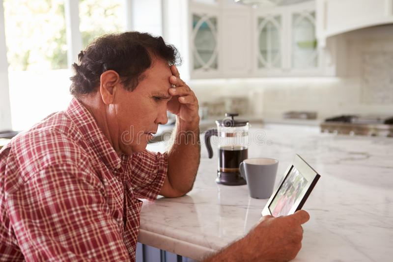 Älterer hispanischer Mann zu Hause, der alte Fotografie betrachtet stockbild