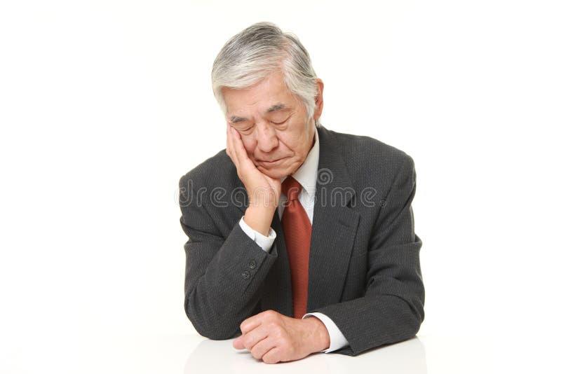 Älterer japanischer Geschäftsmann, der auf dem Tisch schläft stockfoto