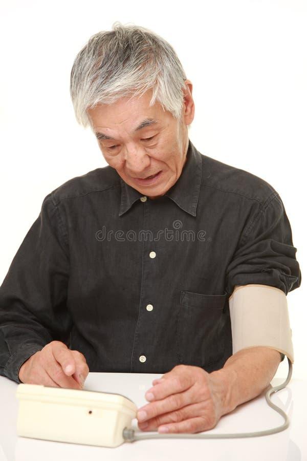 Älterer japanischer Mann, der seinen Blutdruck entsetzt überprüft stockbild
