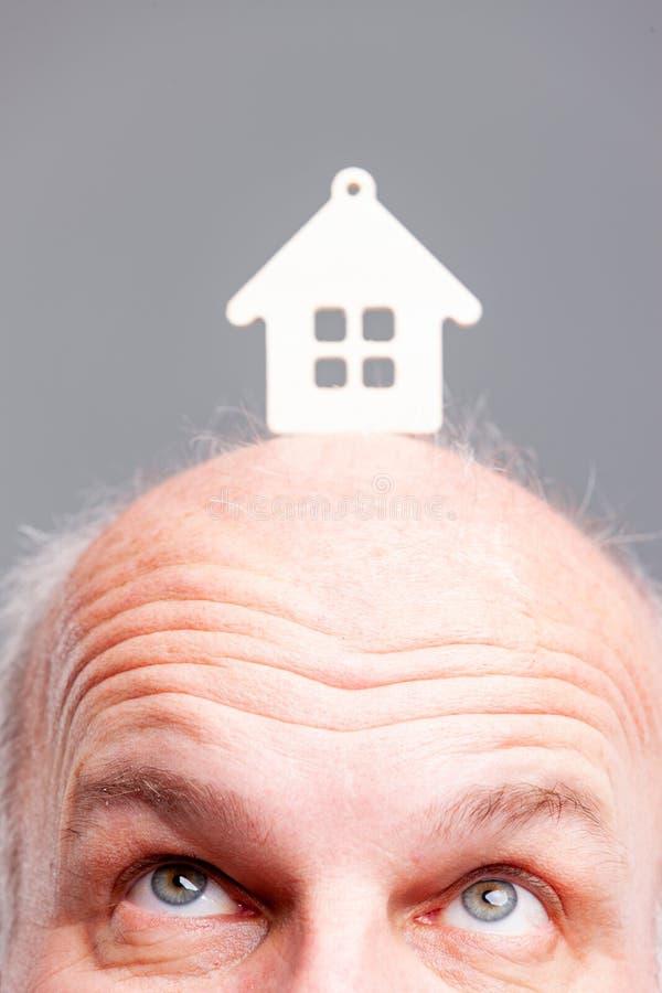 Älterer kahl werdend Mann, der oben einem Musterhaus betrachtet lizenzfreies stockfoto