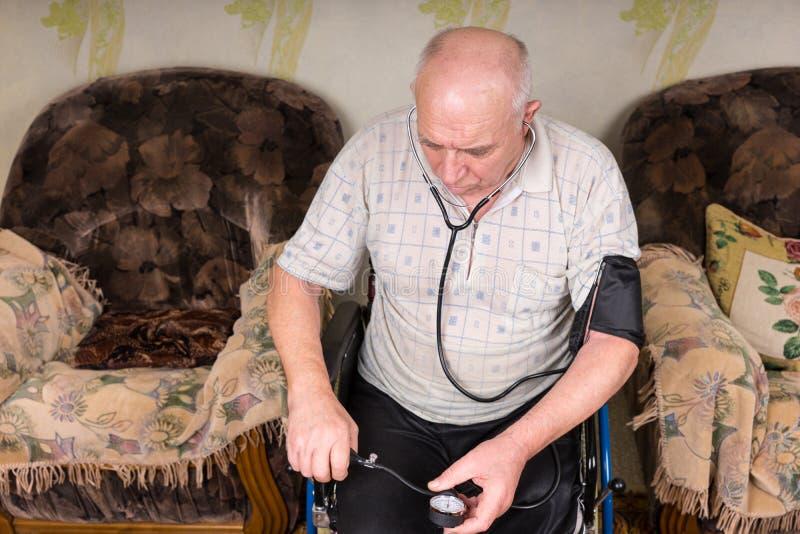 Älterer kahler Mann, der seinen Blutdruck allein überprüft stockfotografie