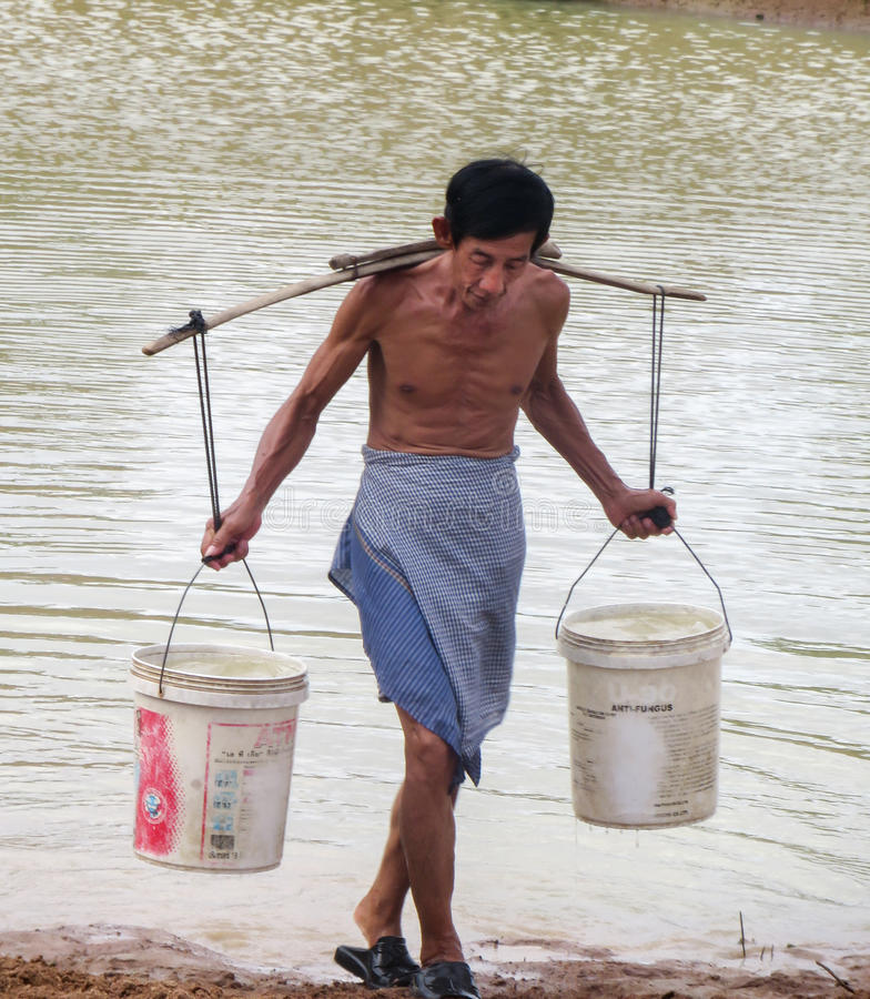 Älterer kambodschanischer Mann-tragendes Wasser stockbilder