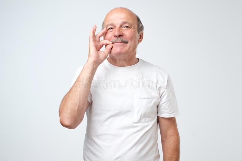 Älterer kaukasischer Mann, der ein Zeichen der schließend Mund- und Ruhegeste tut wie das Schließen seines Munds mit einem Reißve stockbilder