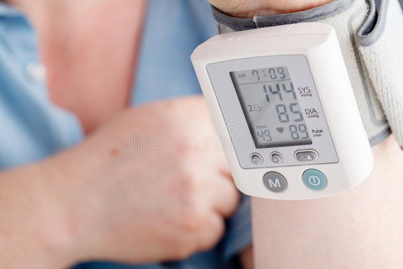 Älterer kaukasischer pensionierter Mann, der zu Hause Blutdruck nimmt stockbilder