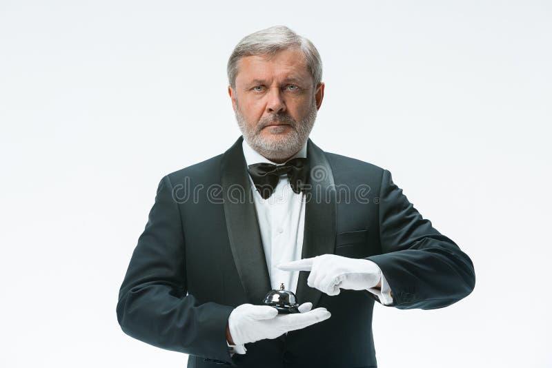 Älterer Kellner, der Glocke hält lizenzfreie stockfotografie