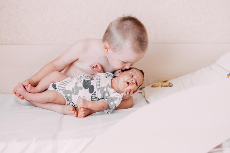 älterer kleiner blonder Kleinkindbruderjunge, der sein kleines Schwesterchen hält stockbild