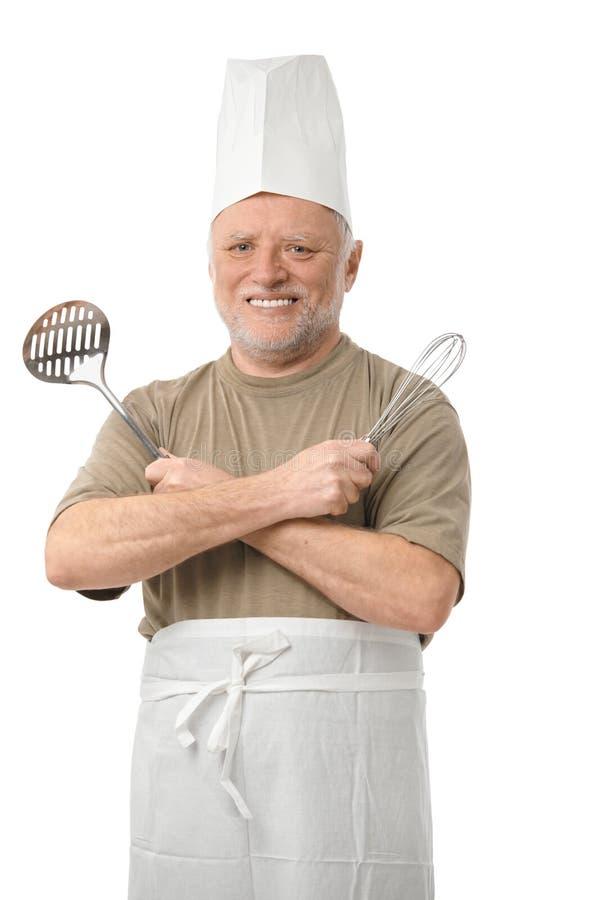 Älterer Koch mit Küchegeräten stockfotografie