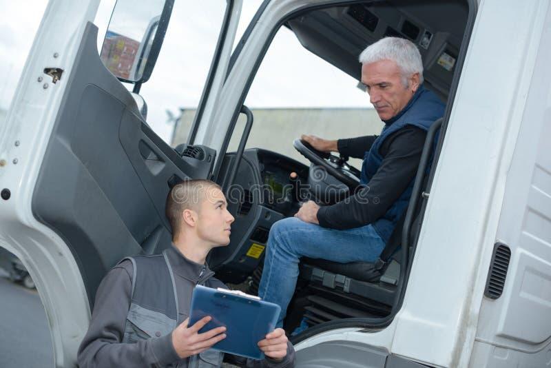 Älterer LKW-Fahrer, der dem Manager nimmt lizenzfreie stockbilder