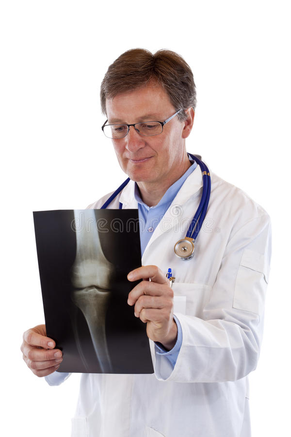 Älterer männlicher älterer Doktor betrachtet Röntgenstrahlbild lizenzfreie stockbilder