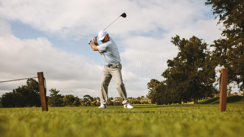 Älterer männlicher Golfspieler, der Schuss nimmt stockbilder