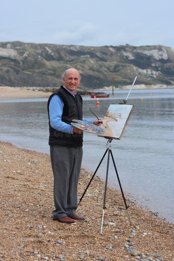 Älterer männlicher Künstleranstrich durch das Meer. lizenzfreie stockfotografie