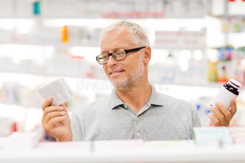 Älterer männlicher Kunde, der Drogen an der Apotheke wählt stockbild