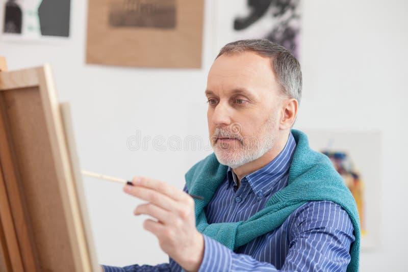Älterer männlicher Maler schafft neues Bild lizenzfreie stockbilder