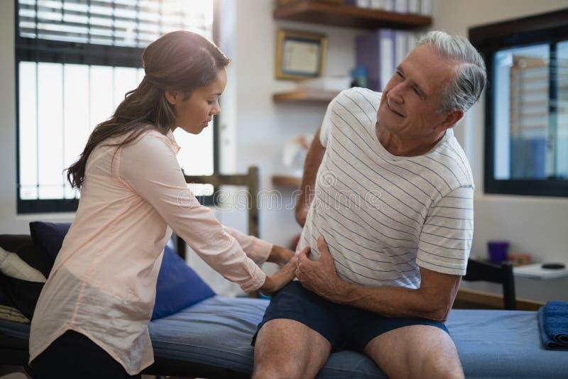 Älterer männlicher Patient, der auf Bett während weiblicher Therapeut zurück überprüft sitzt stockfoto