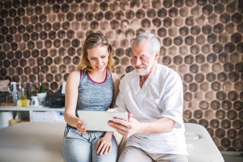 Älterer männlicher Physiotherapeut und junge Frau mit Tablettensitzen lizenzfreies stockfoto