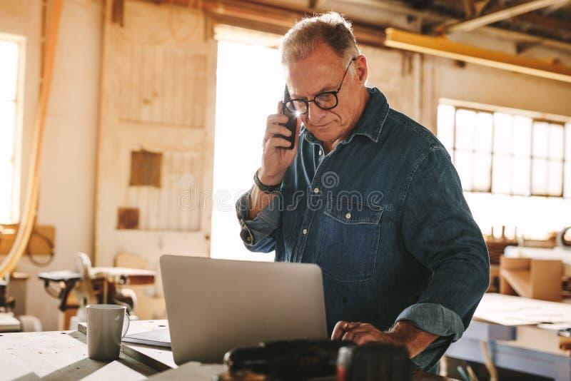 Älterer männlicher Tischler, der in seiner Werkstatt arbeitet stockfotos
