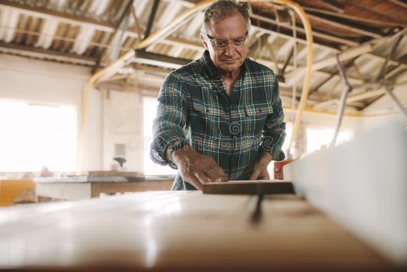 Älterer männlicher Tischler, der an Tabellensägemaschine arbeitet lizenzfreie stockbilder