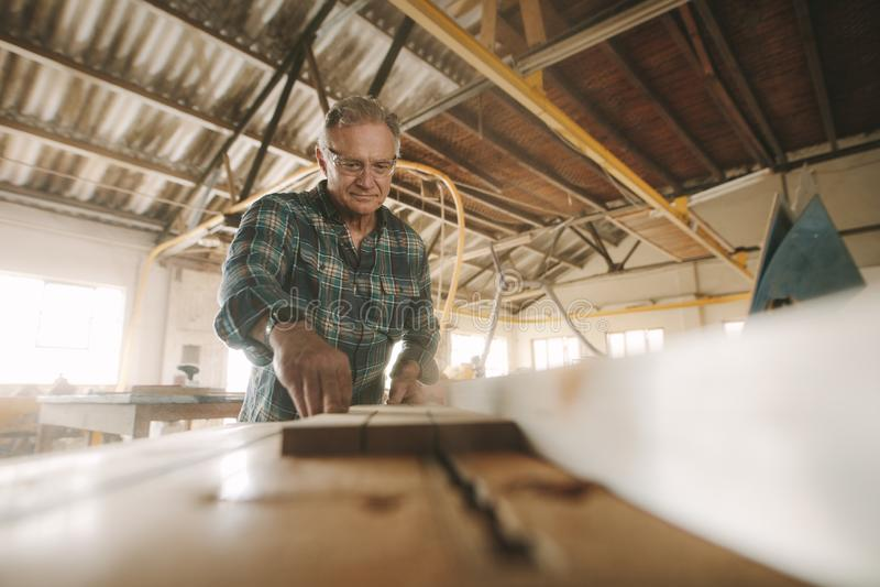 Älterer männlicher Tischler, der in der Zimmereiwerkstatt arbeitet stockfotos