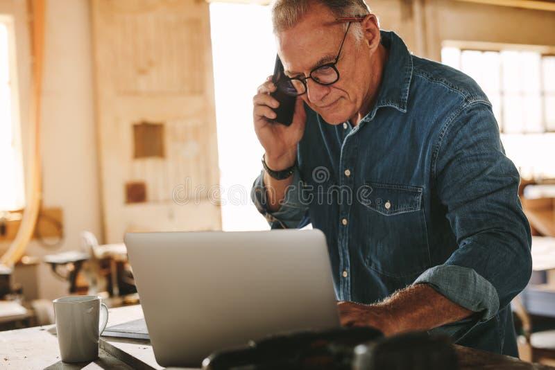 Älterer männlicher Tischler am Telefon stockfoto