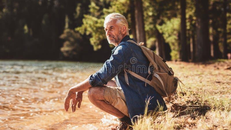 Älterer männlicher Wanderer, der durch einen See sich entspannt und die Ansicht bewundert lizenzfreie stockfotos