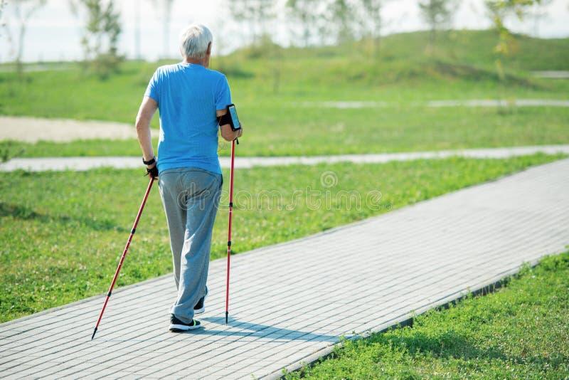 Älterer Mann übender Nordic, der zurück Ansicht geht lizenzfreie stockfotos