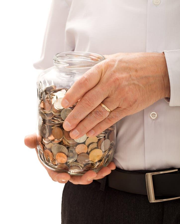 Älterer Mann übergibt Holdingglas mit Münzen lizenzfreies stockfoto