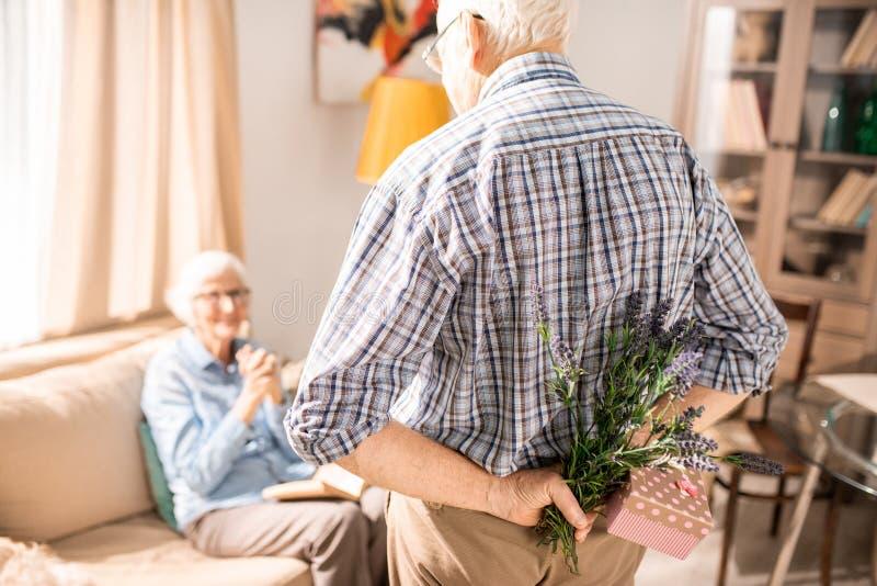 Älterer Mann-überraschende Frau mit Geschenk stockbild