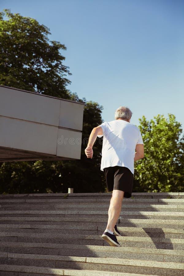 Älterer Mann als Läufer mit Armbinde oder Eignungsverfolger an der Straße der Stadt stockbilder