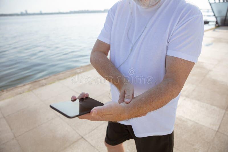 Älterer Mann als Läufer mit Armbinde oder Eignungsverfolger am Flussufer lizenzfreies stockfoto