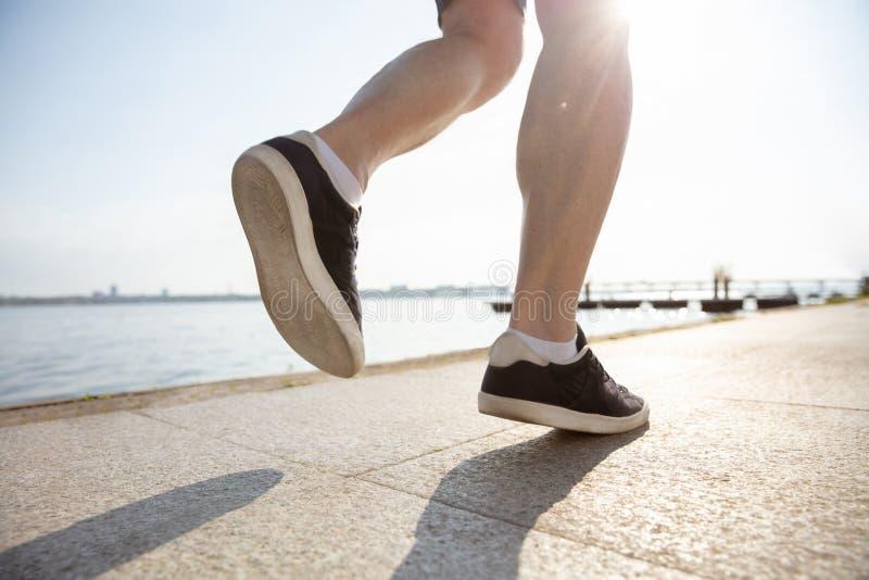 Älterer Mann als Läufer mit Armbinde oder Eignungsverfolger am Flussufer lizenzfreies stockbild