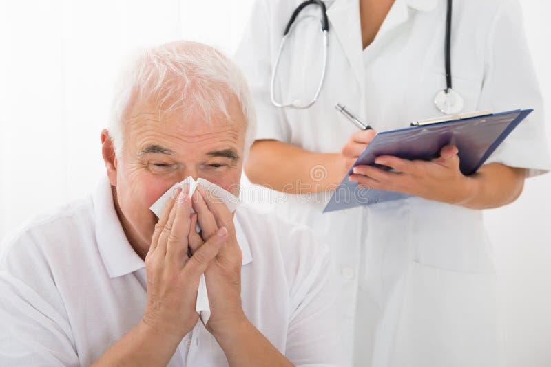 Älterer Mann angesteckt mit der Kälte, die seine Nase in der Klinik durchbrennt lizenzfreie stockbilder