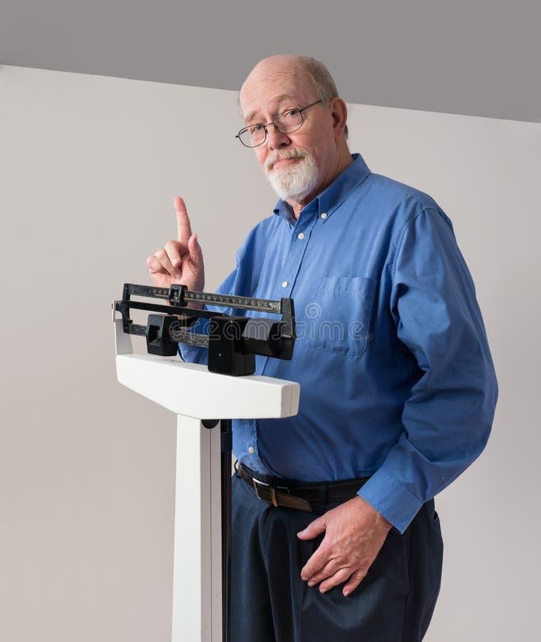 Älterer Mann auf Gewichts-Skala einen Finger halten lizenzfreie stockfotografie