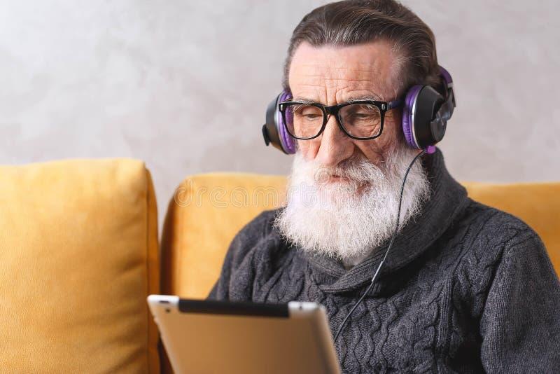 Älterer Mann-aufpassender Film auf dem Tablet-Computer stockfotografie