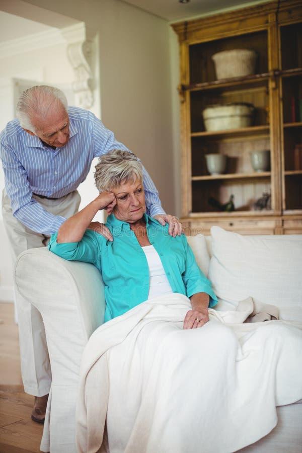 Älterer Mann, der ältere Frau im Wohnzimmer tröstet lizenzfreie stockbilder