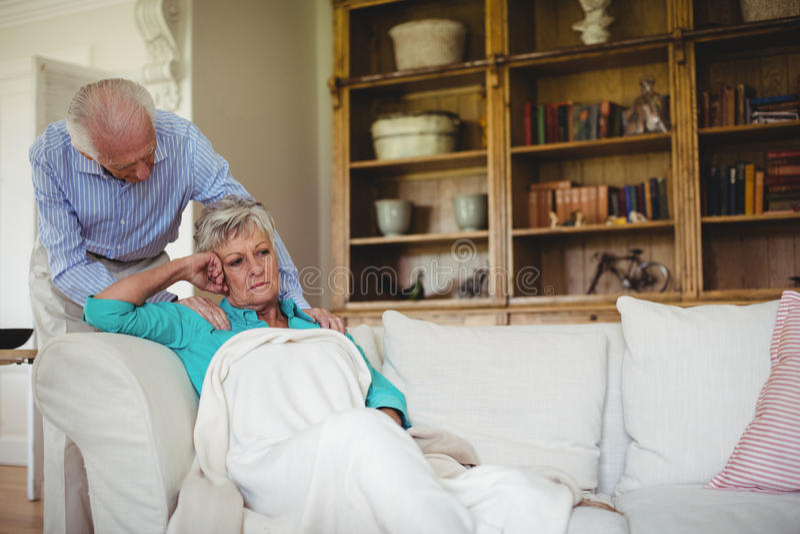 Älterer Mann, der ältere Frau im Wohnzimmer tröstet stockfotos
