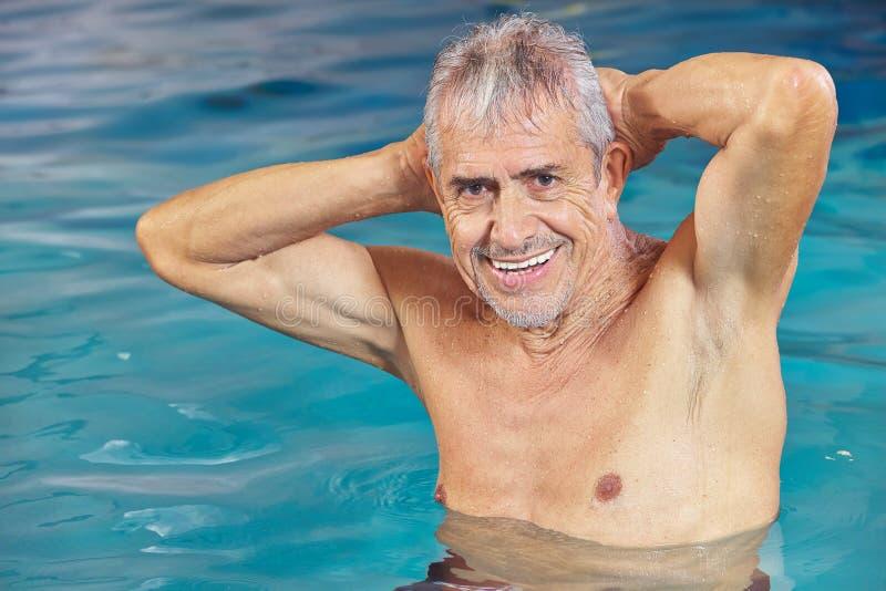 Älterer Mann, der Aquaeignung im Swimmingpool tut stockbilder