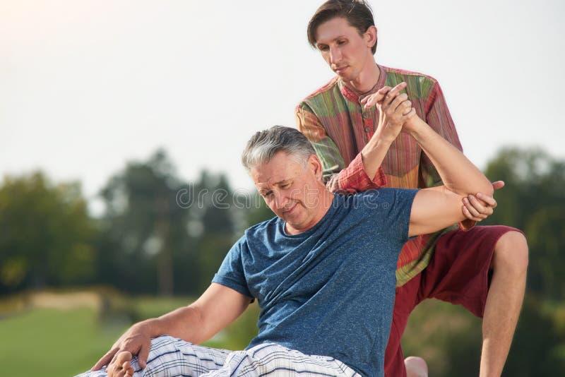 Älterer Mann, der Arm thailändische Massage erhält lizenzfreie stockfotografie