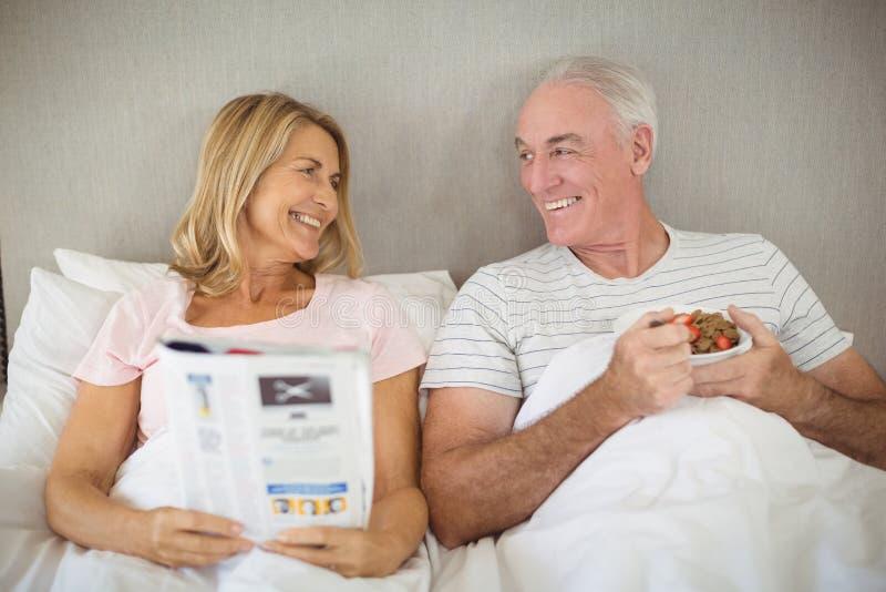 Älterer Mann, der auf Bett frühstückt lizenzfreies stockbild