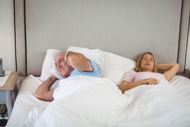 Älterer Mann, der auf Bett liegt und seine Ohren mit Kissen bedeckt stockfotografie