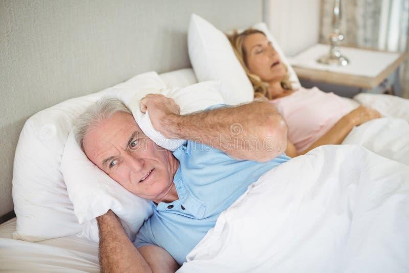 Älterer Mann, der auf Bett liegt und seine Ohren mit Kissen bedeckt stockbilder