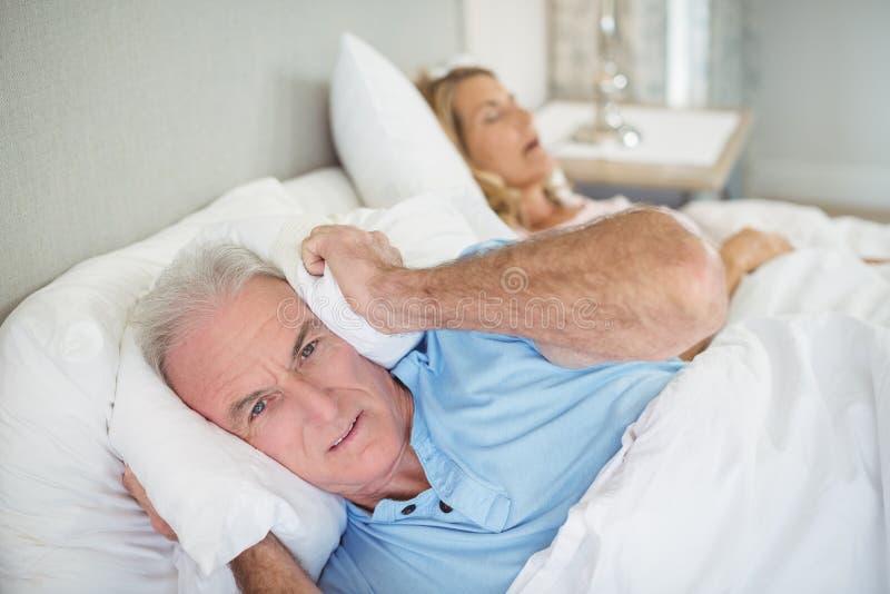 Älterer Mann, der auf Bett liegt und seine Ohren mit Kissen bedeckt stockbild