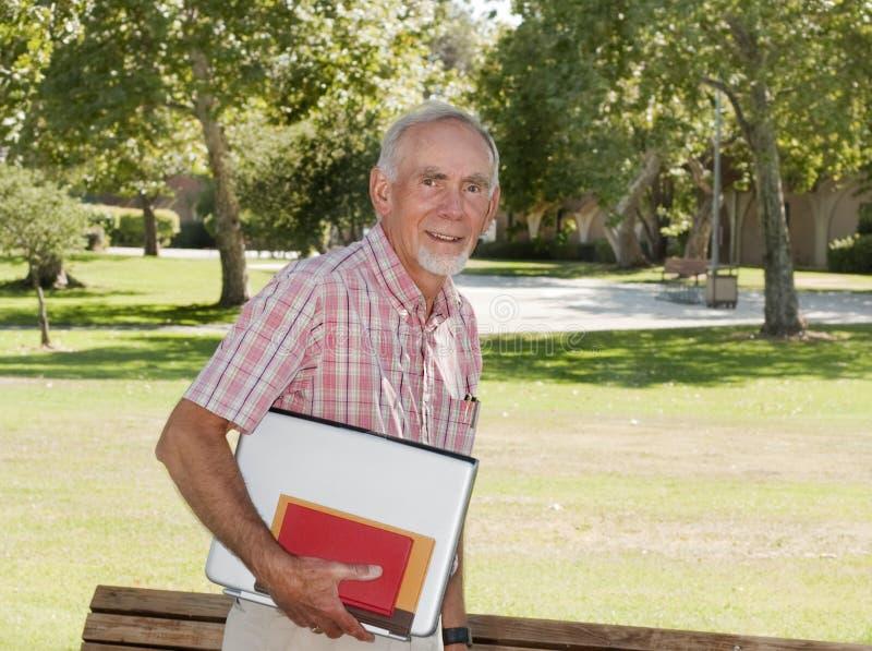 Älterer Mann, der auf Campus klassifizieren geht stockbilder