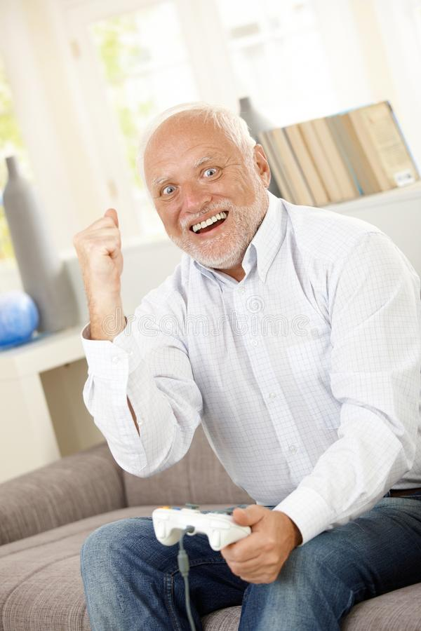 Älterer Mann, der auf Computerspiel gewinnt stockbilder