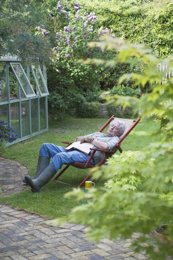 Älterer Mann, der auf Deckchair im Hinterhof schläft lizenzfreie stockfotografie